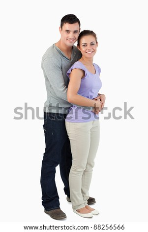 Side view of young male holding his girlfriend against a white background - stock photo