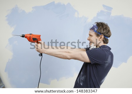 Side view of young man holding drill as gun against wall in unrenovated house - stock photo