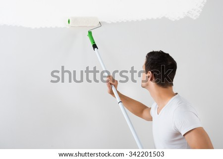 Side view of young man painting wall with paint roller at home - stock photo