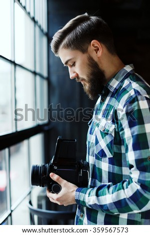 Side view of young man, wearing in blue and white checkered shirt, standing near the window with retro camera in his hands and take a picture, in cafe, waist up - stock photo