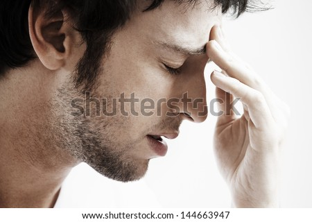 Side view of young man with headache touching forehead on white background - stock photo