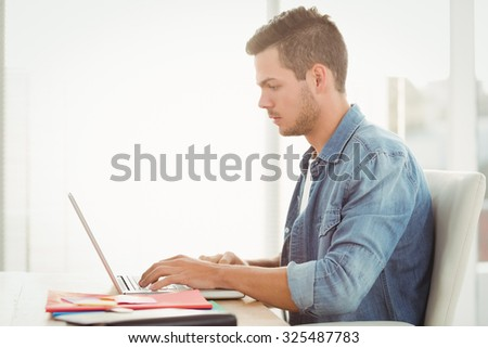 Side view of young man working on laptop while sitting at desk - stock photo