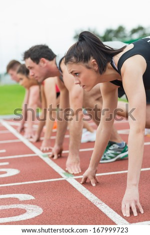 Side view of young people ready to race on track field - stock photo