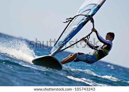 Side view of young windsurfer close-up - stock photo