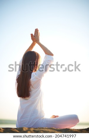 Side view of young woman doing yoga against clear sky outdoors - stock photo