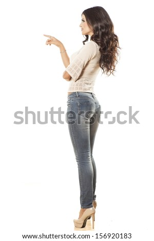 side view of young woman in jeans  touching imaginary object - stock photo