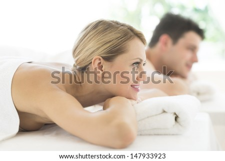 Side view of young woman looking away while relaxing at spa with man in background - stock photo