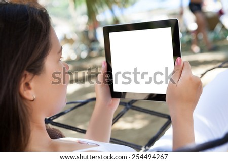 Side view of young woman using digital tablet at beach - stock photo