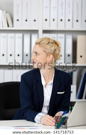 Side view on blond and beautiful young businesswoman at work - stock photo