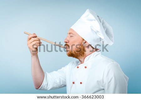 Side view photo of young male chef in white uniform. Head-cook tasting food from wooden spoon with his eyes closed and standing against grey background - stock photo