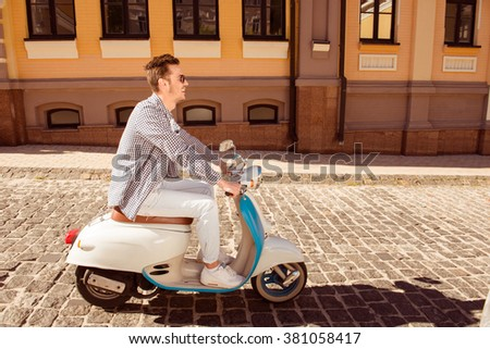 Side view photo of young man riding a motor bike - stock photo