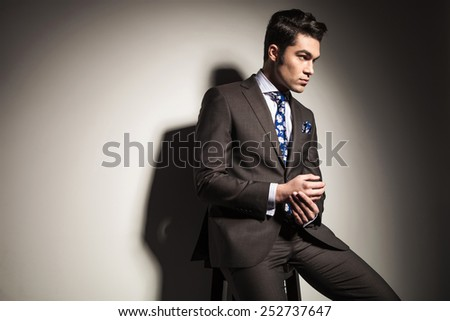 Side view picture of a elegant business man looking away from the camera while sitting on a stool. - stock photo