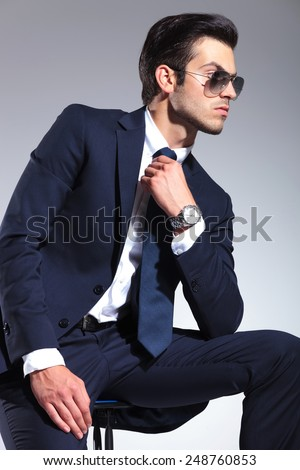 Side view picture of a elegant business man sitting while fixing his tie, looking away from the camera. - stock photo