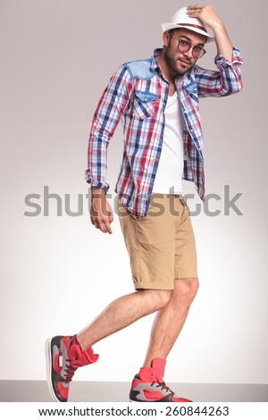 Side view picture of a fashion man looking at the camera while walking and holding one hand on his hat. - stock photo
