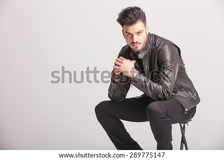 Side view picture of a handsome casual man holding his hands together while sitting on a stool. - stock photo