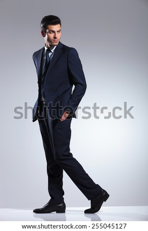 Side view picture of a young business man walking on grey studio background with his hands in pockets. - stock photo