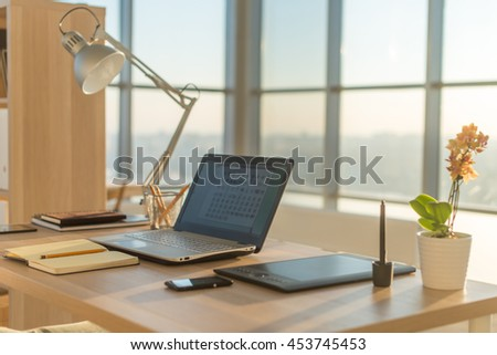 Side view picture of studio workplace with blank notebook, laptop. Designer comfortable work table, home office - stock photo
