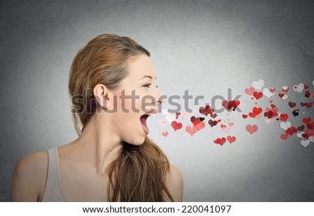 Side view portrait beautiful woman sending kisses, red hearts coming out of open mouth, isolated grey wall background. Positive emotions, facial expression, feelings, life perception. valentines day - stock photo