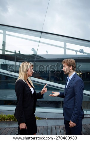 Side view portrait business people discussing work during break, caucasian businesswoman serious speaking to a colleague while they standing outside office, angry boss talk to her employee gesturing  - stock photo