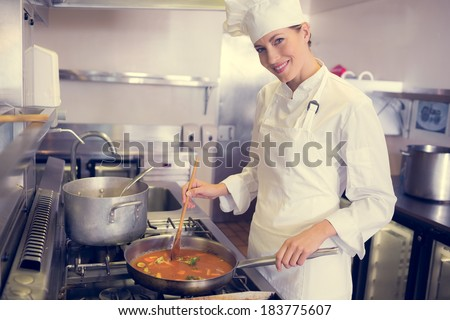 Side view portrait of a female cook preparing food in the kitchen - stock photo