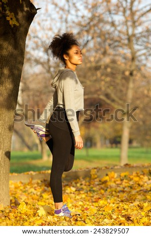Side view portrait of a fit young african american woman stretching muscles outdoors  - stock photo
