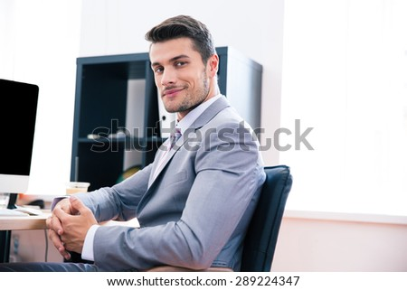Side view portrait of a happy businessman sitting on the office chair and looking at camera - stock photo