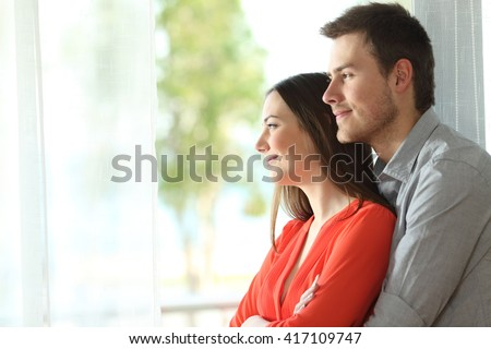 Side view portrait of a happy marriage standing hugging and looking outdoors through a window at home or hotel room with a green background - stock photo