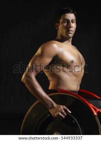 Side view portrait of a paraplegic cycler against black background - stock photo