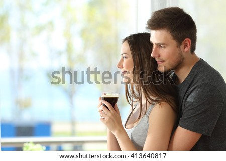 Side view portrait of a pensive couple or marriage hugging and looking outdoors through a window of an hotel room or home with the sea in the background - stock photo