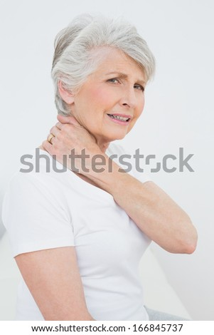 Side view portrait of a senior woman suffering from neck pain over white background - stock photo