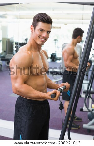 Side view portrait of a shirtless young muscular man using triceps pull down in gym - stock photo
