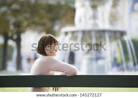 Side view portrait of a smiling young woman sitting on bench in front of blurred fountain - stock photo