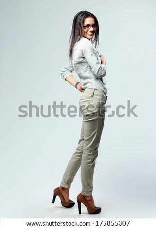Side view portrait of a young cheerful businesswoman standing on gray background - stock photo