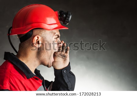 Side view portrait of angry coal miner shouting against a dark background - stock photo