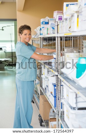 Side view portrait of female nurse smiling while working in storage room of hospital - stock photo