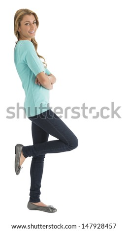 Side view portrait of happy young Caucasian woman with arms crossed leaning over white background - stock photo