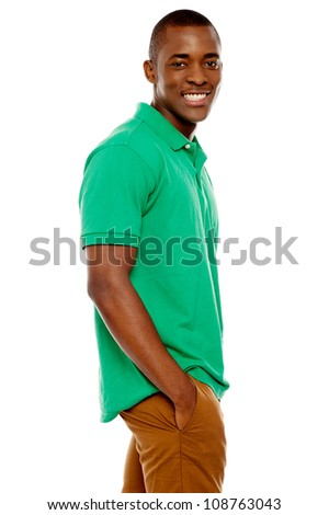 Side view portrait of smiling casual african guy posing with hands in pocket - stock photo