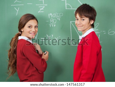 Side view portrait of teenage school students standing against board in classroom - stock photo