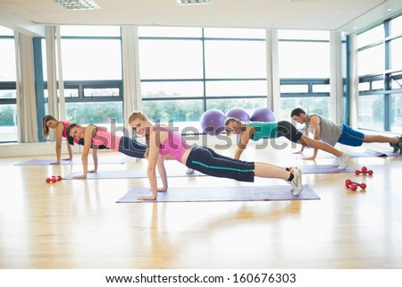 Side view portrait of trainer with class doing push ups in bright fitness studio - stock photo