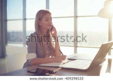 Side view portrait of young businesswoman having business call in office, her workplace, writing down some information. Woman talking on mobile phone, asking questions, looking at pc screen. - stock photo