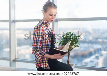 Side view portrait of young woman sitting, looking down, reading the book, learning at light room in morning with her torso turned.  - stock photo