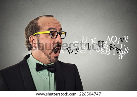 Side view profile portrait middle aged business man talking symbols alphabet letters coming out of his mouth isolated grey wall background. Human face expression. Communication intelligence concept  - stock photo