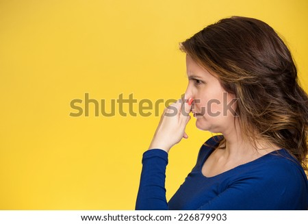 Side view profile portrait middle aged woman covers pinches her nose with hand looks with disgust, something stinks bad smell situation isolated yellow background. Human face expression body language - stock photo