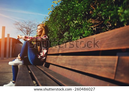 Side view seated woman on the bench enjoying nature in sunny day outdoors, charming young girl relaxing in the spring park, female student relaxing at campus, flare sun light - stock photo