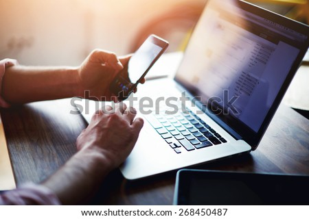 Side view shot of a man's hands using smart phone in interior, rear view of business man hands busy using cell phone at office desk, young male student typing on phone sitting at wooden table, flare - stock photo