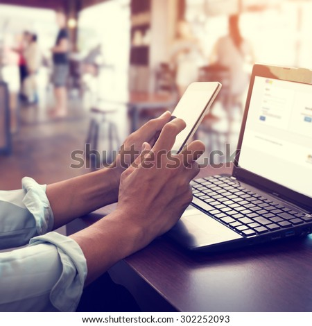 Side view shot of young business man working on his laptop and using smart phone sitting at wooden table in a coffee shop with retro filter effect - stock photo