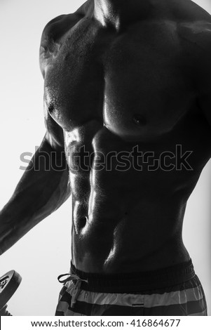 Side-view silhouette of young muscular athletic sexy shirtless hot man posing showing sport body with cool pectoral abs muscle strong breast biceps studio black and white. Beads sweat training gym.  - stock photo