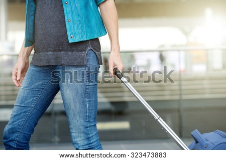 Side view woman pulling suitcase at airport - stock photo