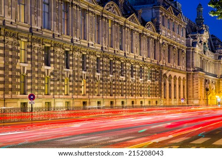 Side wing of the Louvre museum in Paris, capital of France, at night with the busy traffic in front of it leaving red and white light trails in the evening - stock photo