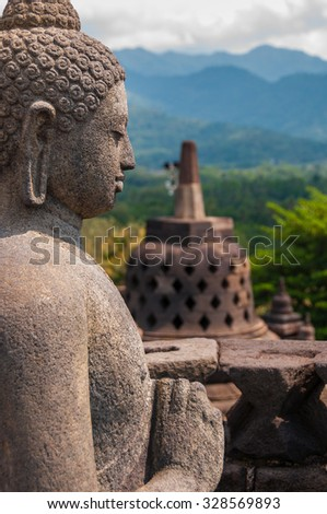 Sideview of a Buddha and a Stupa made of stone at Borobudur - stock photo
